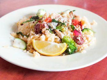 Ryzova paella s lososom, cuketou, citronom, brokolicou, redkovkou, posypana bylinkami.