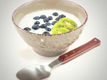 Biely domaci jogurt v miske s cucoriedkami a kiwi.