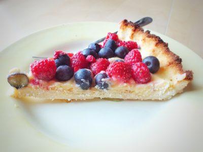 Vyrez citronoveho kolaca na tanieri s lesnym ovocim.