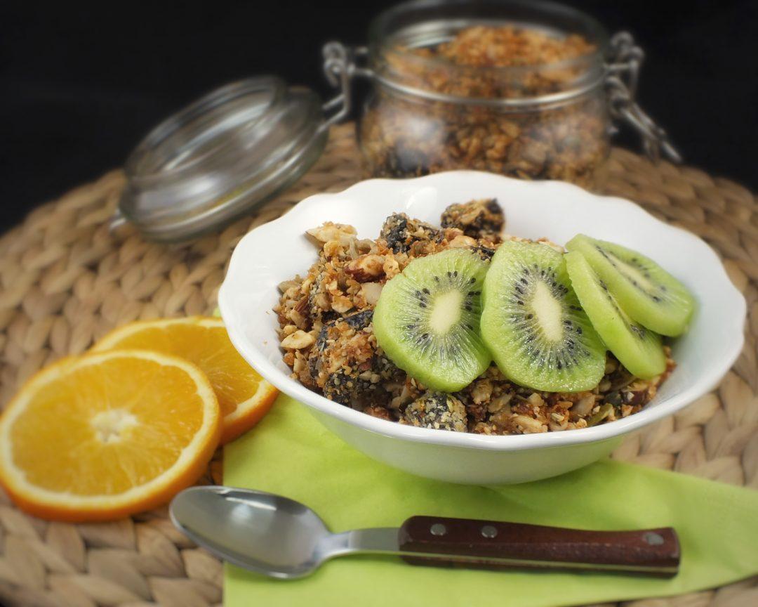 Paleo granola na ranajky z orieskov mandli a kesu so semienkami. Ozdobene s kiwi a pomarancom.