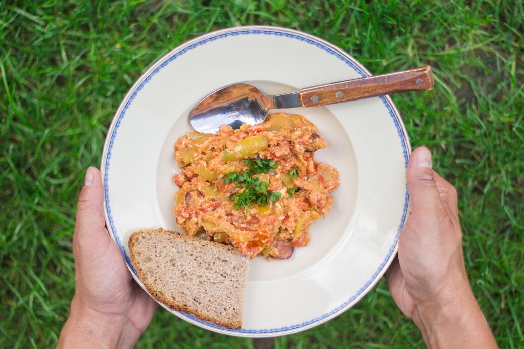 Leco na tanieri nad travou s lyzicou a kvaskovym chlebom