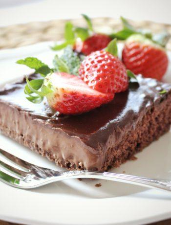 Čokoládový koláč s polevou z čokoládového francúzskeho krému na tanieri s jahodami.