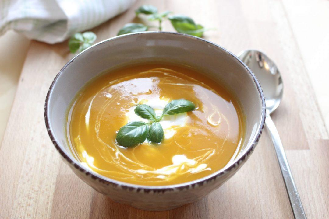 Kremova batatova polievka v tanieri na drevenej podlozke s bazalkou a kyslou smotanou