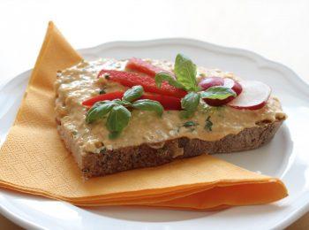 Brynzdova pomazanka na tanieri s oranzovou servitkou, ozdobena bazalkou, cervenou paprikou a nakrajanymi redkvickami