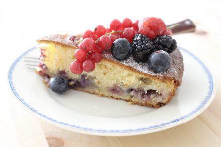 Vyrez mascarpone kolac s lesnym ovocim na tanieri s vidlickou