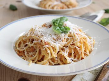 Spaghetti s omackou z pecenych paprik na tanieri ozdobene parmezanom a bazalkou.