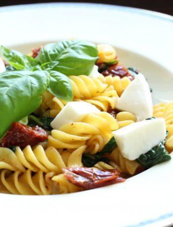 Fusili tricolore v detaile so sušenými paradajkami, mozzarellou a bazalkou.