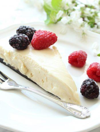 Oreo cheesecake s kremom z arasidoveho masla s malinami a cernicami na bielom tanieri s vidlickou