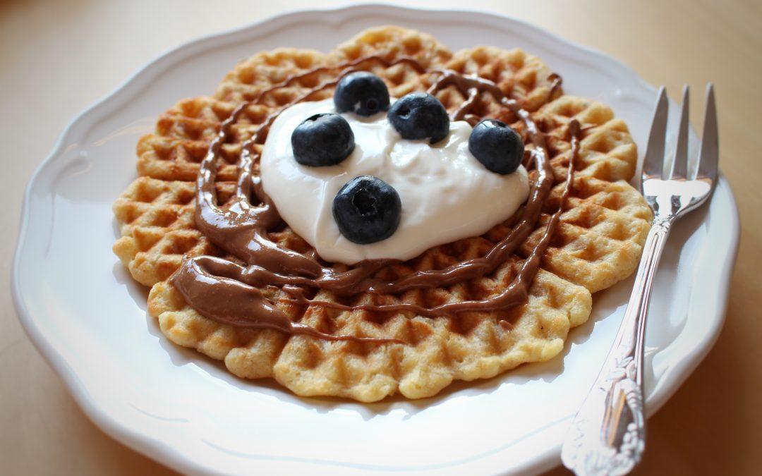 Ovsene wafle s orieskovym maslom, domacim pribinackom a cucoriedkami s vidlickou v pozadi na bielom tanieri.