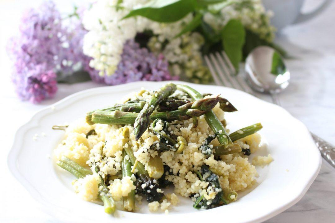 Jarny zeleny kuskus so sparglou, spenatom, zelenou fazulkou a hraskom na bielom tanieri v pozadi s orgovanom.