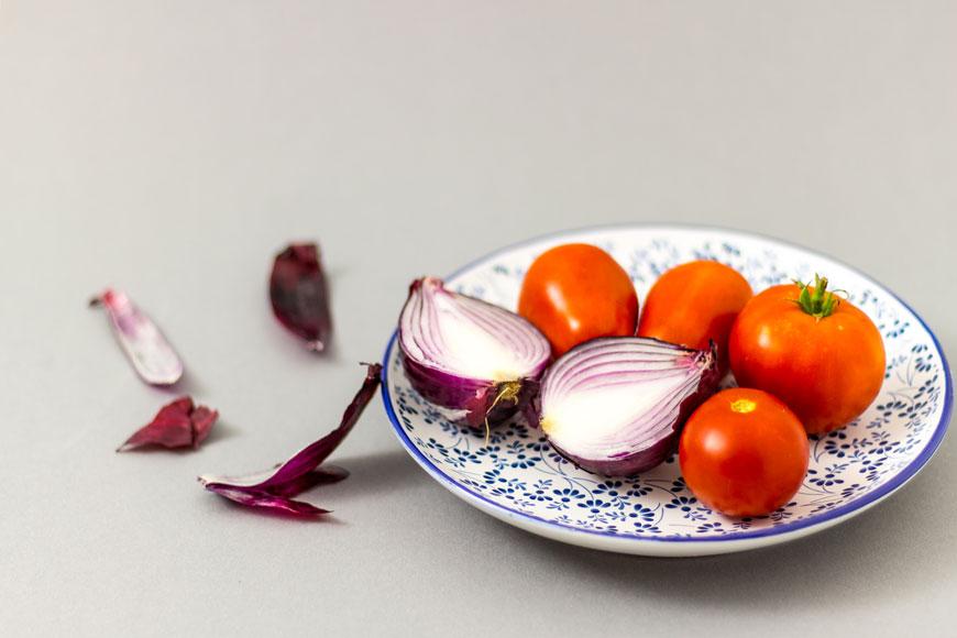 Suroviny na paradajkovy salat na tanieri: paradajky a cervena cibula.