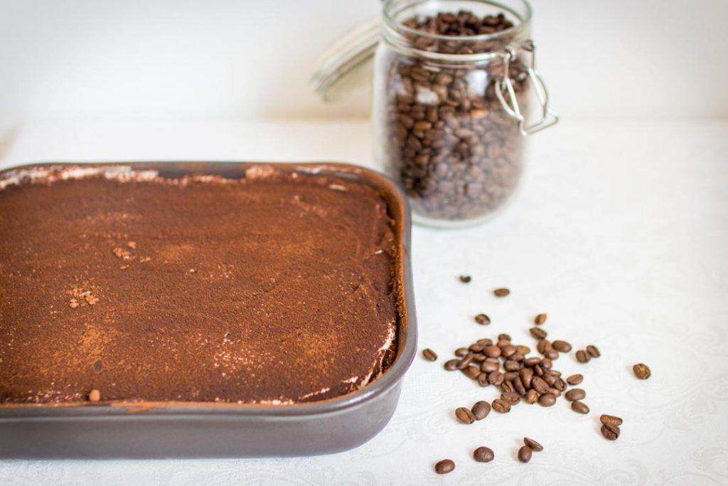 Cele tiramisu posypane kakaom so zrnkami kavy na bielom obruse.