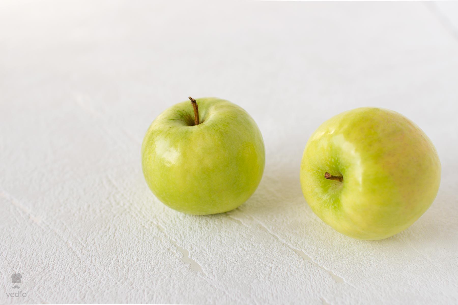 Dve zelene jablka na bielom podklade