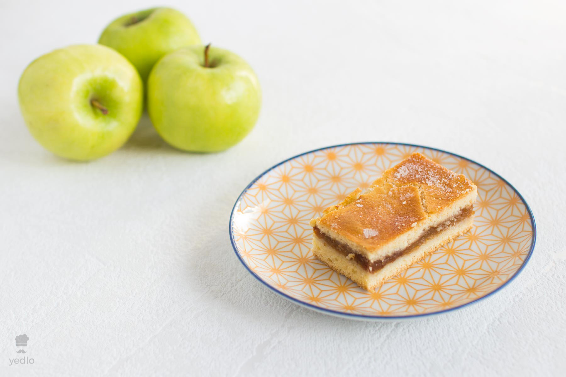 Jablkove pyte na tanieriku s 3 zelenymi jablkami v pozadi.