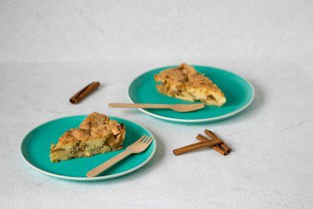 Jablkova sarlotka kusky na zelenych tanieroch s drevenymi vidlickami.