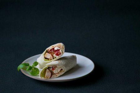 Plneny wrap kuratom, zeleninou na bielom tanieri s bazalkou.