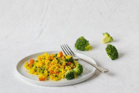 Ryza opekana s baby karotkou, hraskom a kukuricou posypana parmezanom na bielom tanieri.
