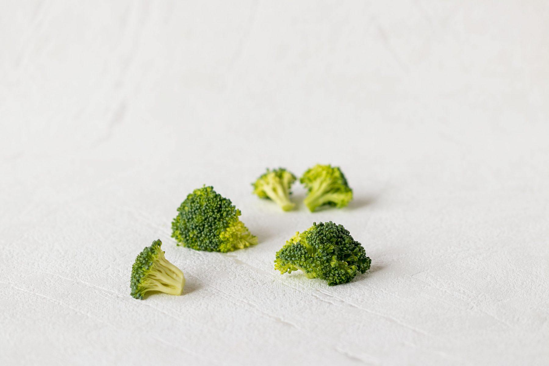 Male ruzicky brokolice na bielom podklade.