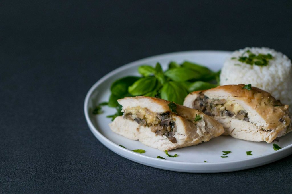 Plnene kura hribikmi a syrom s ryzou a salatom na bielom tanieri.