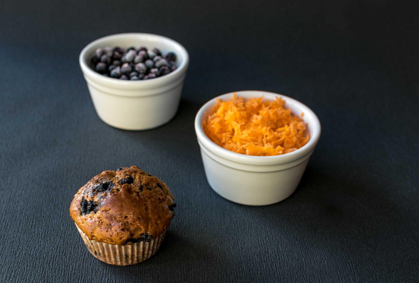 Muffin s dvoma bielymi miskami s nastruhanou mrkvou a cucoriedkami.